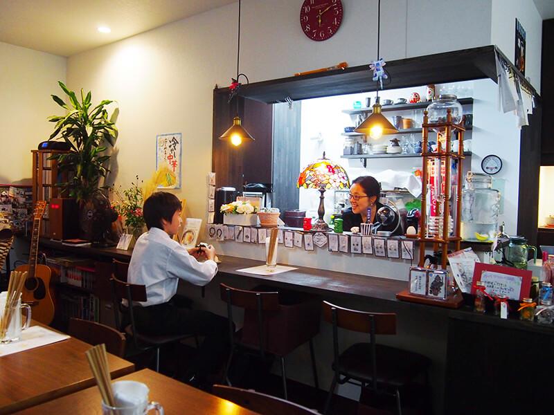 子どもたちと話しながら食事を提供する稲生さん。子どもたちも塾とは違うリラックスした表情