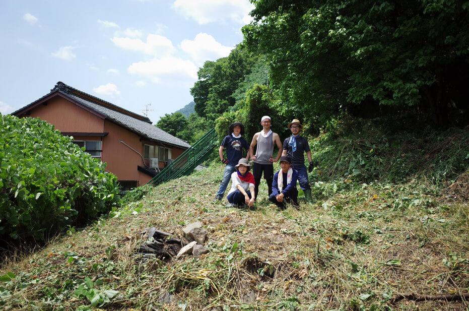 2016年8月の〈すけろくガーデン〉。手付かずの空き家の屋根(写真左)には、緑が生い茂っていた。まずは有志の協力を得て、裏山の整地からプロジェクトがスタート(写真提供:『まち畑プロジェクト』)