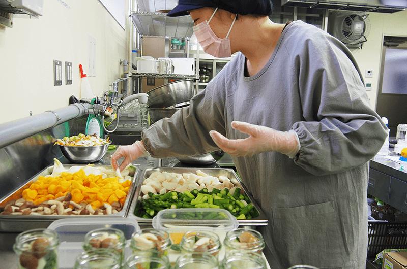仕込み作業中の北村さん。あらかじめバランスを考えた上でそれぞれの野菜の大きさと入れ方を決めて野菜をカットし、瓶に詰めていきます